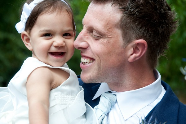 Picture of a groom holding a young girl by Fiona Kelly Photography