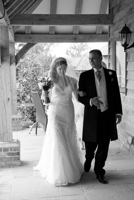 Black and white picture of a bride being led by the arm by Fiona Kelly Photography