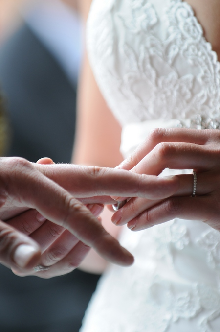 Picture of a bride placing a wedding ring on her groom's finger by Fiona Kelly Photography