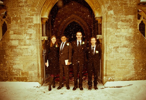 Picture of a bridal party standing in the doorway of a church in the snow by Anneli Marinovich Photography