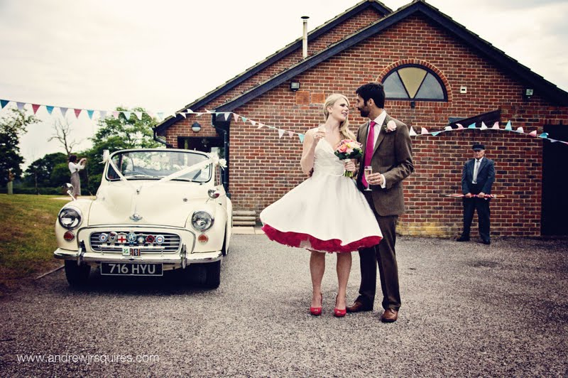 Couple standing by a wedding car by Andrew J R Squires Photography