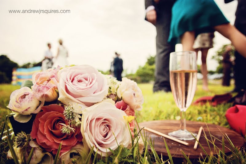 Champage and a bridal bouquet of roses by Andrew J R Squires Photography