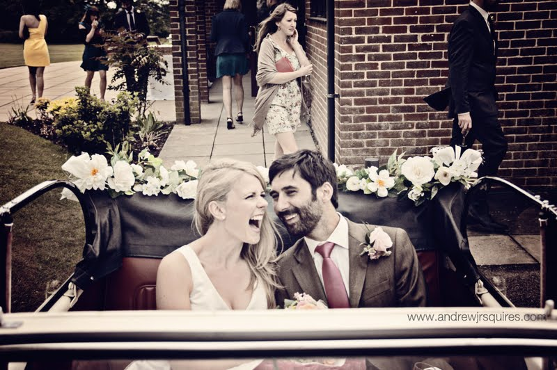 Couple laughing in the back of a Morris Minor wedding car by Andrew J R Squires Photography