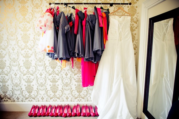 Bridesmaid dresses and wedding gown hanging on a rail - Martins Kikulis Photography