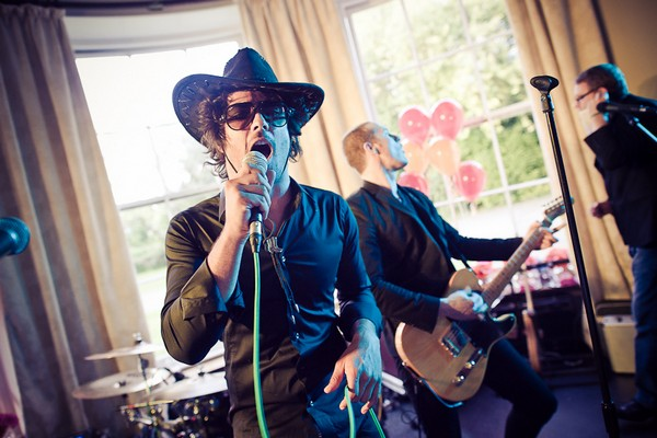 Wedding guest in cowboy hat singing with band - Martins Kikulis Photography