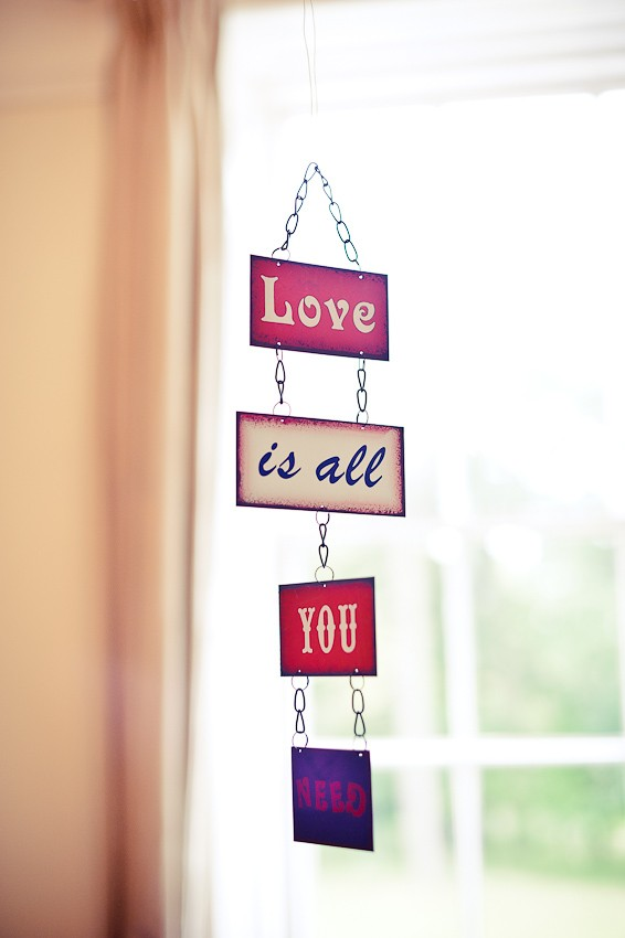 Hanging 'Love is all you need' sign - Martins Kikulis Photography