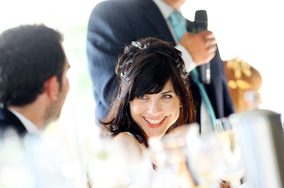 Bride smiling during a wedding speech by Martin Beddall Photography