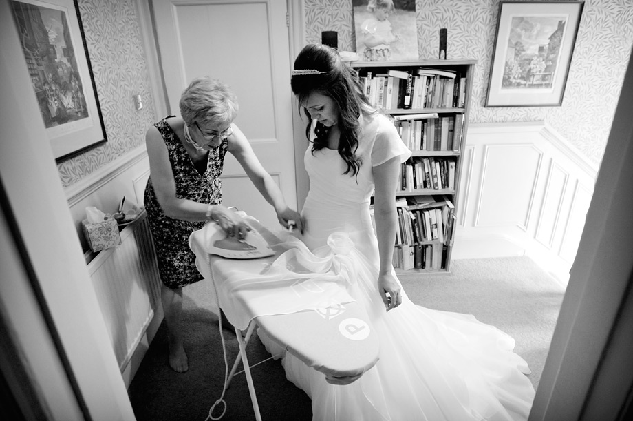 Bride having her wedding dress ironed by Martin Beddall Photography