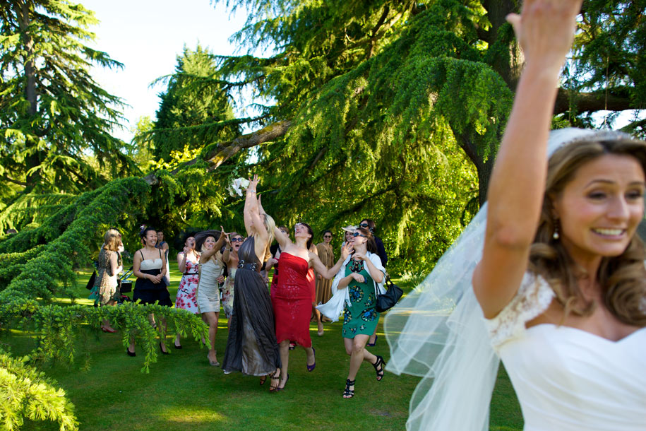 Bride throwing her bouquet by Martin Beddall Photography