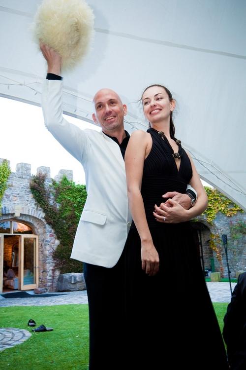 Groom waving white fluffy hat - Sam Gibson Wedding Photography