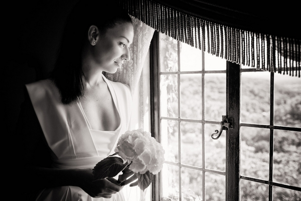 Bride holding her bouquet looking out of the window - Sam Gibson Wedding Photography