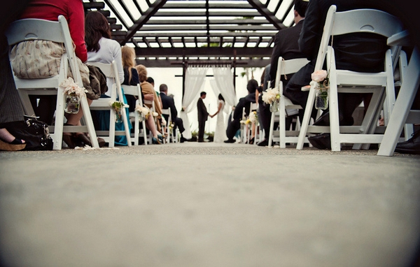 Wedding ceremony viewed through rows of chairs - Picture by Captured by Aimee