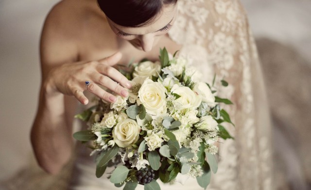 Bride looking at bouquet - Picture by Laura McCluskey Photography
