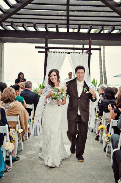Bride and groom walking from ceremony with Chuppah wrapped around them - Picture by Captured by Aimee