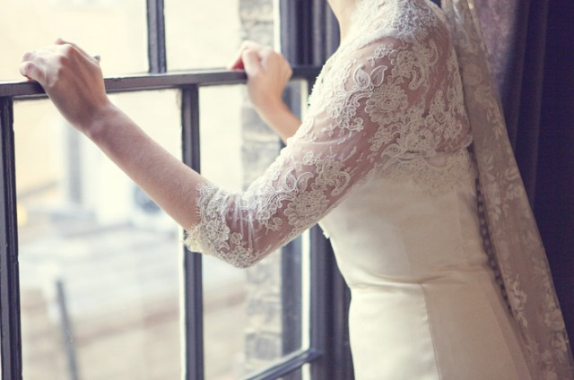 Bride standing at window - Picture by Laura McCluskey Photography