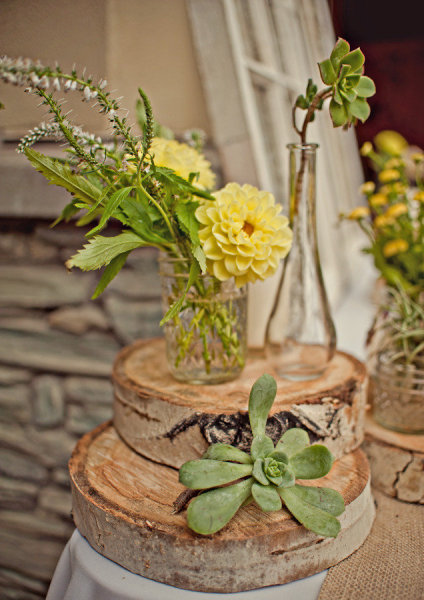 Yellow flowers in vase on a log - Picture by Captured by Aimee