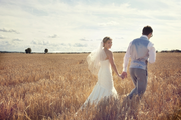 Bride and groom walking through corn fields - Picture by Chasing Moments Photography