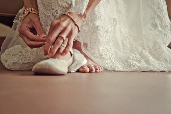 Bride putting on ballet shoes - Picture by Captured by Aimee