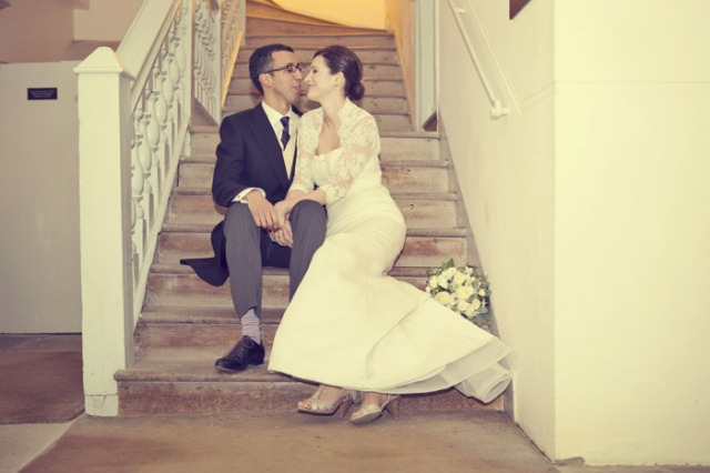 Bride and groom sitting on stairs - Picture by Laura McCluskey Photography