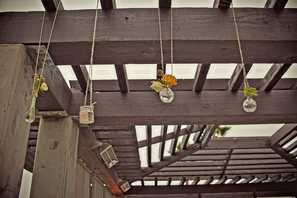 Small vases of flowers hanging from beam - Picture by Captured by Aimee