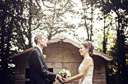Bride and groom holding hands facing each other outside a shed - Picture by Andrew J R Squires Photography