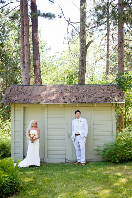 Bride and groom standing in front of shed - Picture by Laura Ivanova Photography