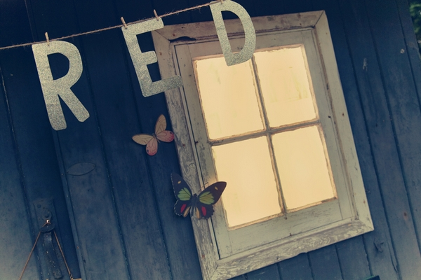 Red letters hanging in front of shed window - Picture by Ian Shoots Weddings