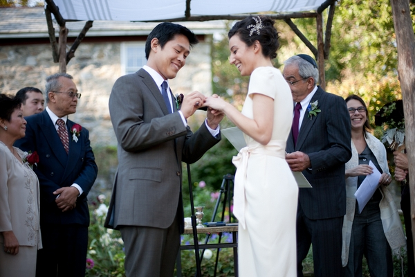 Groom placing ring on bride's finger - Picture by Levi Stolove Photography