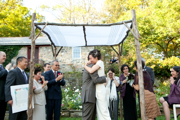 Bride and groom hug under Chuppah - Picture by Levi Stolove Photography