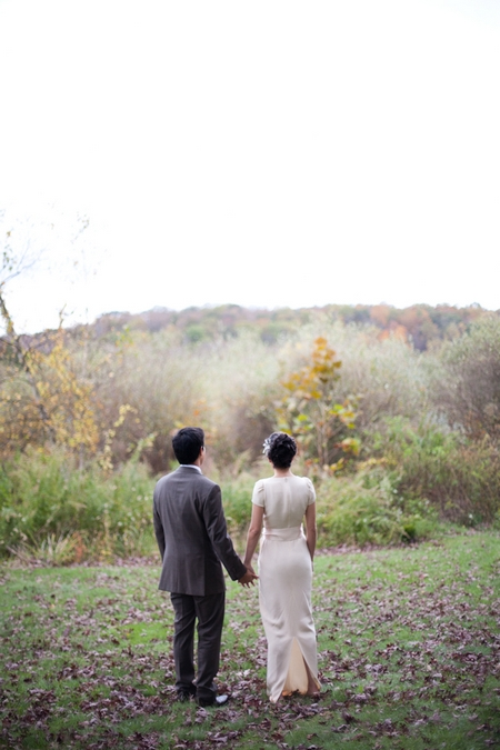 Bride and groom holding hands looking at view - Picture by Levi Stolove Photography