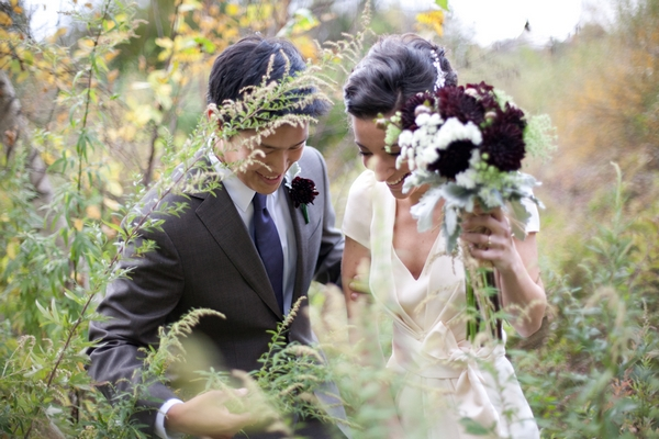 Bride and groom looking at fern - Picture by Levi Stolove Photography