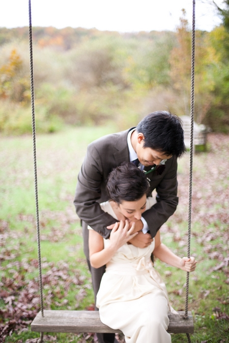 Groom with arms around bride on swing - Picture by Levi Stolove Photography