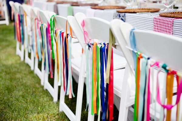 Colourful ribbons hanging from wedding chairs - Picture by Laura Ivanova Photography