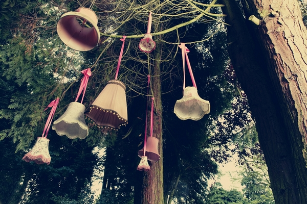 Lamp shades hanging from trees - Picture by Ian Shoots Weddings