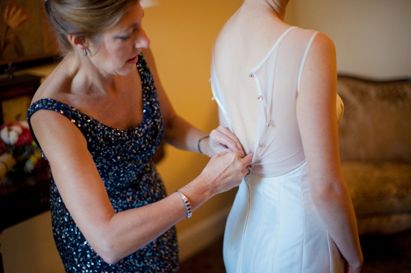 Bride having back of wedding dress done up for her - Picture by Rojo Foto Design