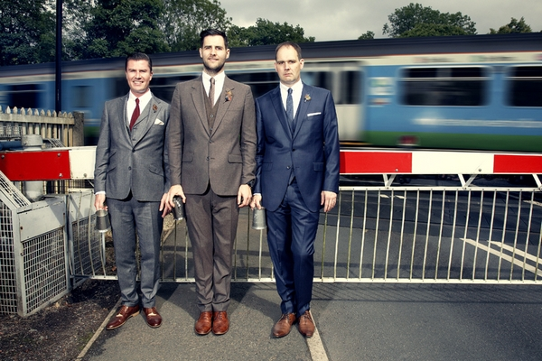 Groomsmen standing in front of railway as train goes past - Picture by Ian Shoots Weddings