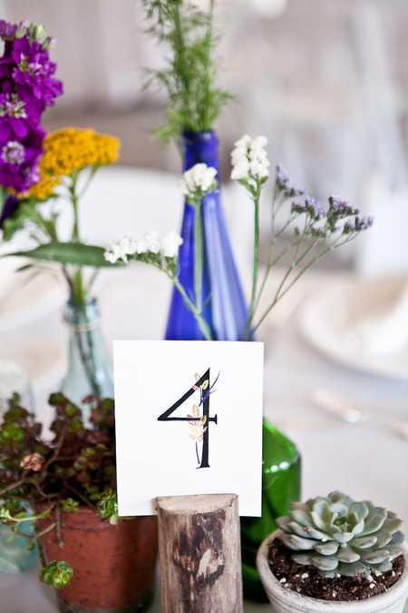 Table number bottles and pot plants on wedding table - Picture by Levi Stolove Photography