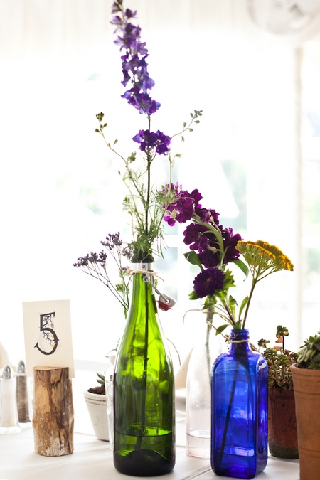 Bottles pot plants and table number on wedding table - Picture by Levi Stolove Photography
