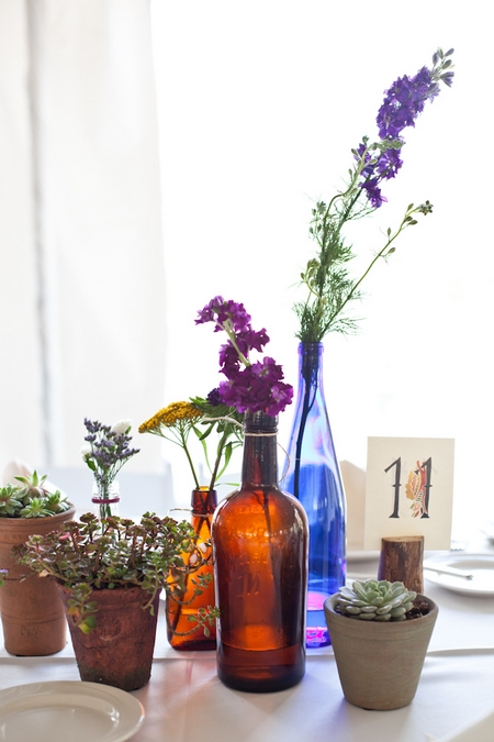 Wedding table with pot plants and coloured bottles - Picture by Levi Stolove Photography