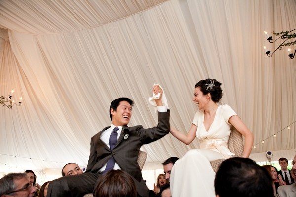 Bride and groom being held aloft on chairs - Picture by Levi Stolove Photography