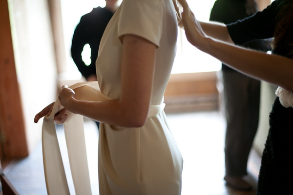 Bride doing up ribbon on her wedding dress - Picture by Levi Stolove Photography