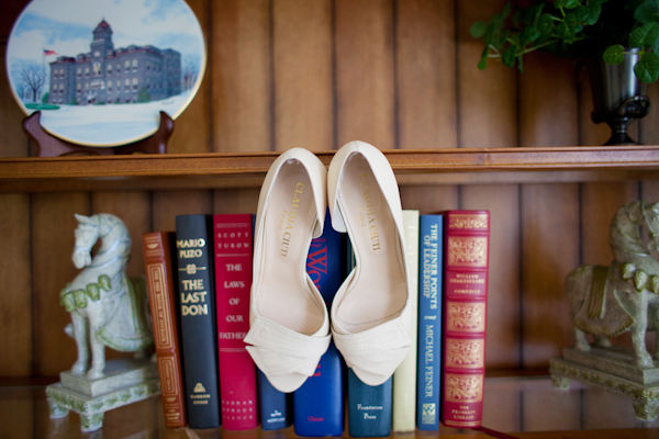 Bridal shoes hanging from bookcase - Picture by Rojo Foto Design