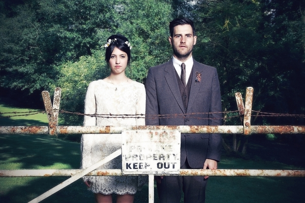 Vintage bride and groom standing behind a gate - Picture by Ian Shoots Weddings