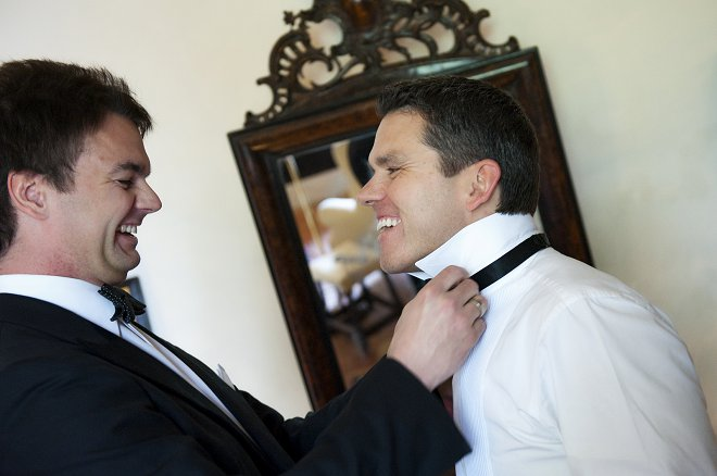 Best man doing up groom's bow tie - Picture by Gill Maheu Photography