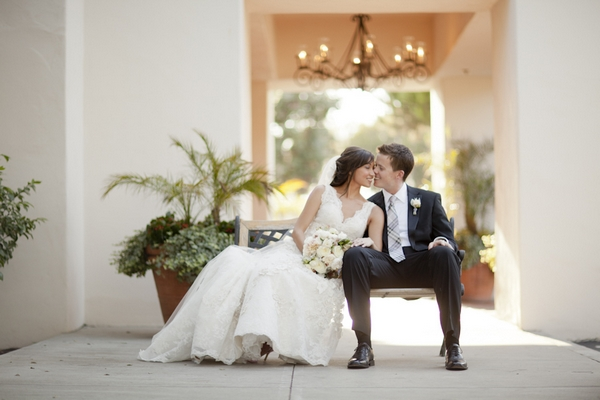 Bride and groom sitting on bench - Picture by Allyson Magda Photography