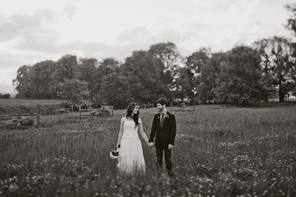 Bride and groom walking in a field - Picture by Jonas Peterson Photography