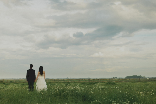 Back of bride and groom standing in field - Picture by Jonas Peterson Photography