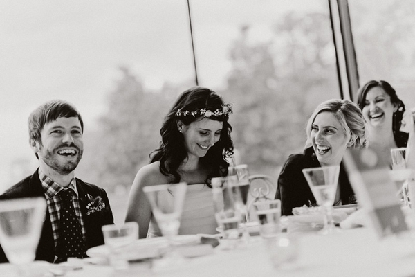Bride and groom smiling during wedding speech - Picture by Jonas Peterson Photography