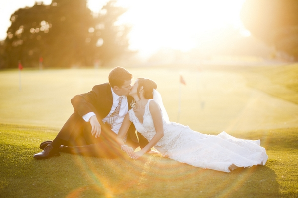 Bride and groom sitting on golf course - Picture by Allyson Magda Photography