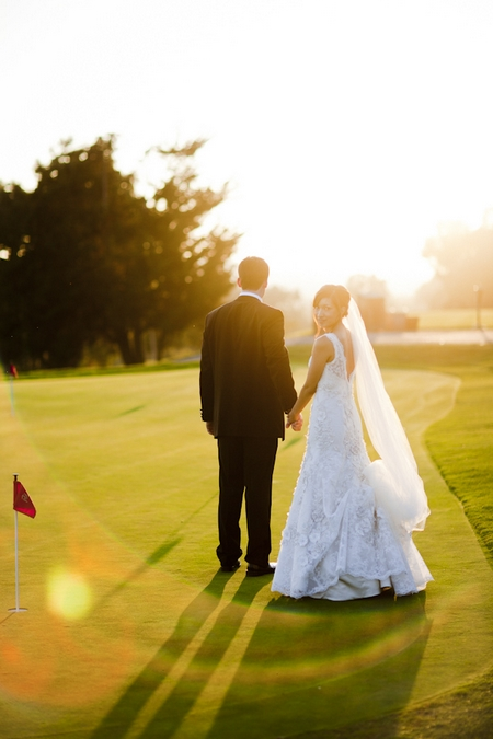 Bride and groom holding hands on golf course - Picture by Allyson Magda Photography